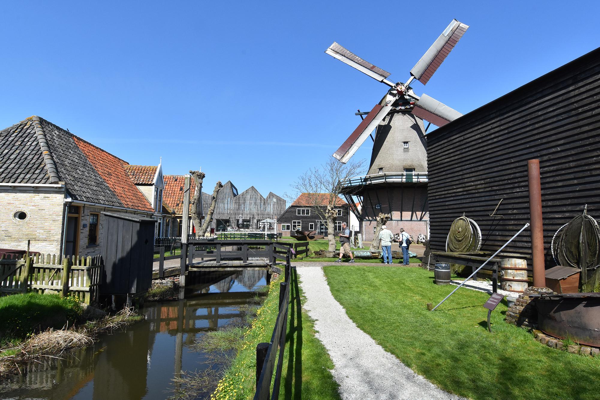 Het buitenterrein van Museum Kaap Skil met oude huizen en de molen VVV Texel