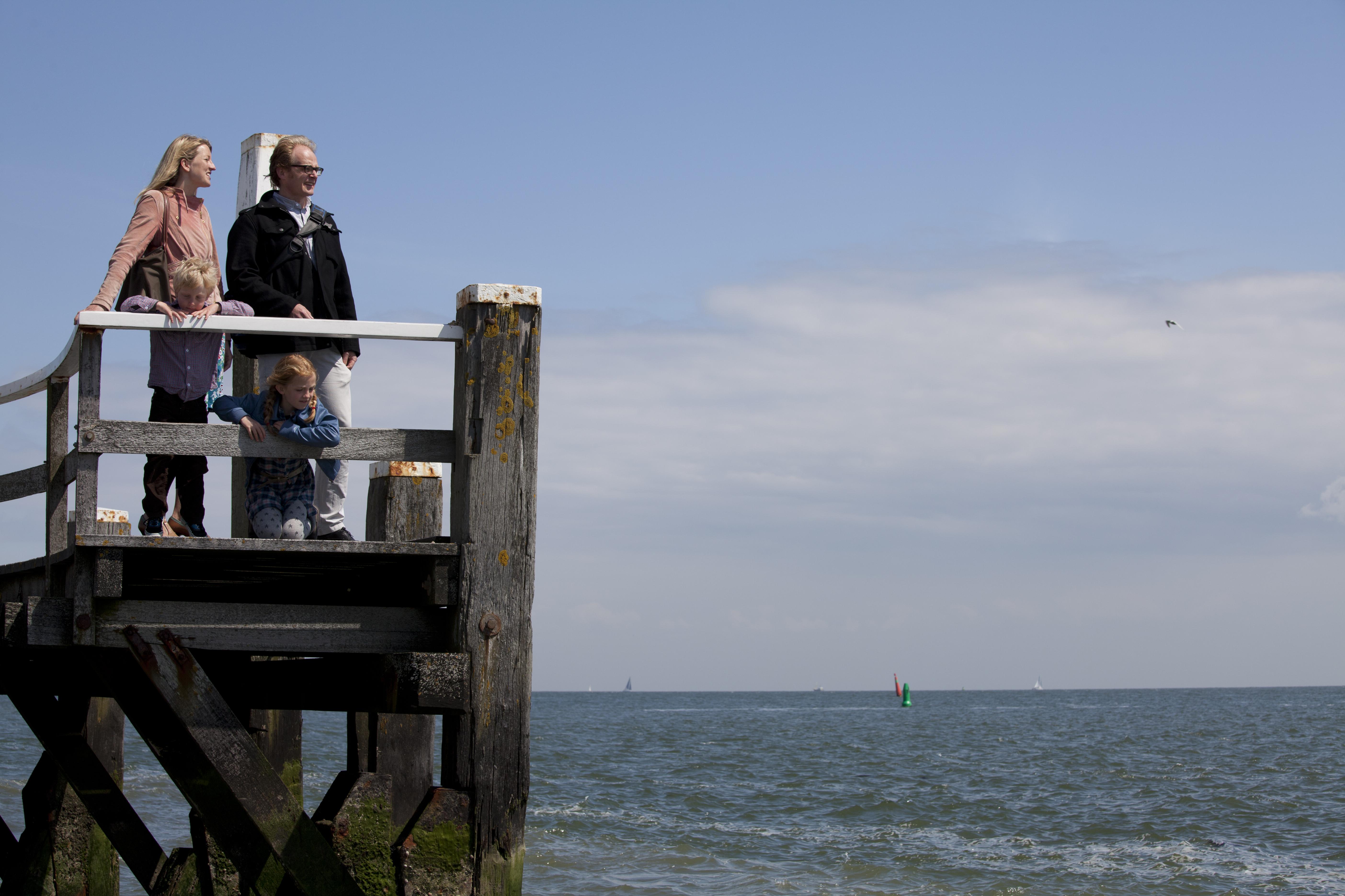 Gezin op de steiger bij de haven van Oudeschild VVV Texel fotograaf Tessa Jol