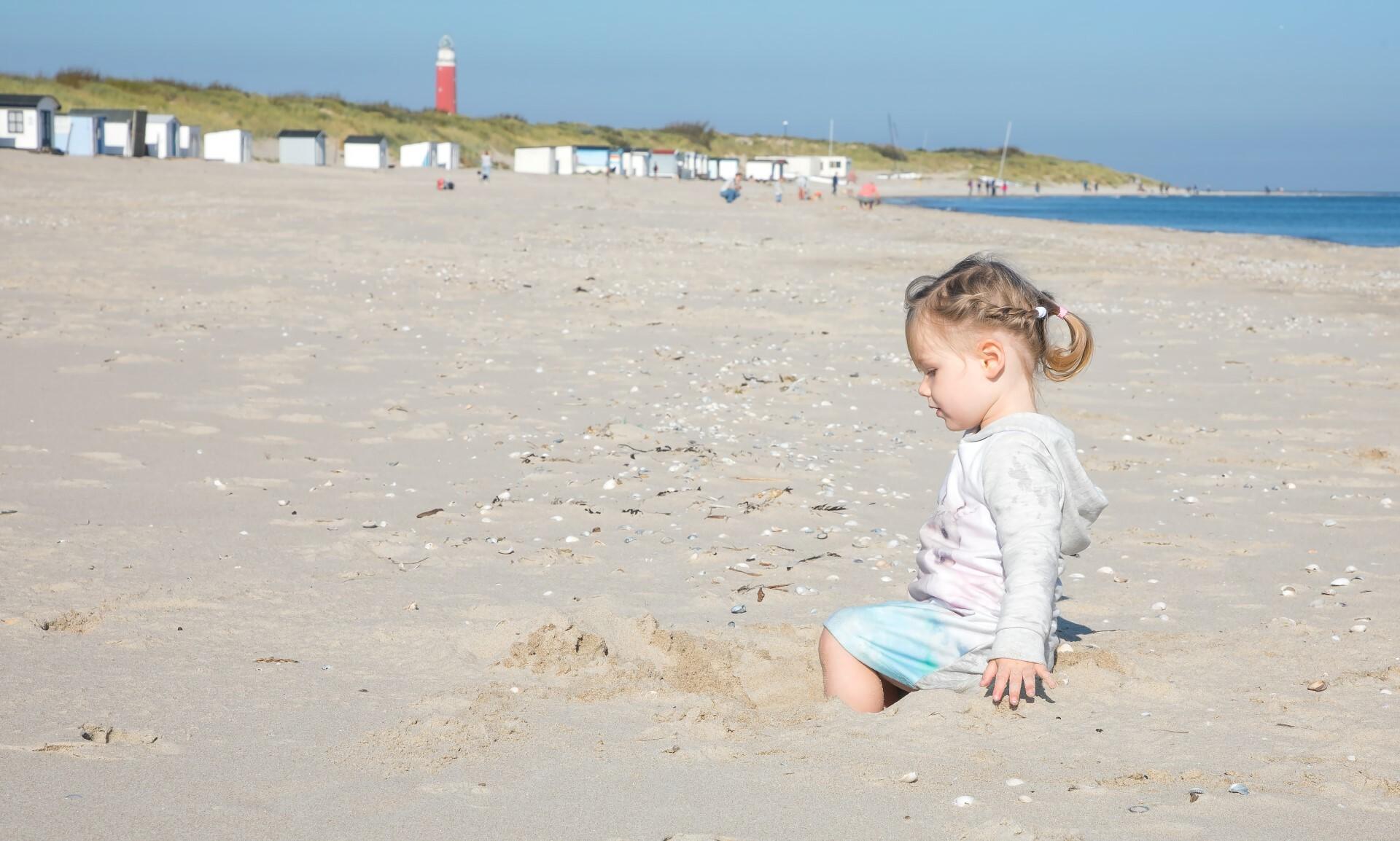 Kindje speelt op het strand bij de vuurtoren VVV Texel fotograaf Justin Sinner
